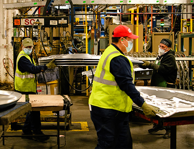 In the foreground a worker with a red hat, ear plugs, safety vest and mask walks across the photo. In the background two workers in PPE carry four sheets of silver metal