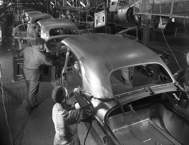 Black and white historic photo of workers using drills and inspecting vehicles in a production line