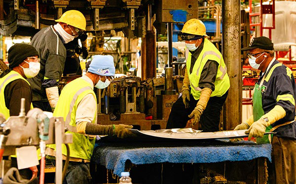 Five men in PPE around a silver sheet of metal. Two men hold it while the three other men survey it.