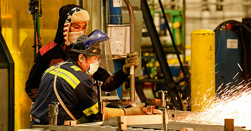 Two workers in PPE including face masks, ear plugs, safety glasses and gloves working on a welding machine with sparks flying to the right