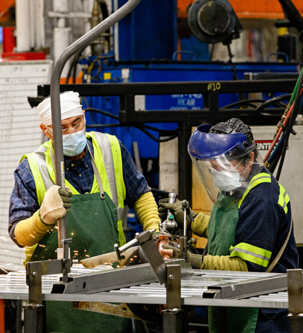 Two workers in PPE including face masks, safety glasses and aprons work with welding equipment.