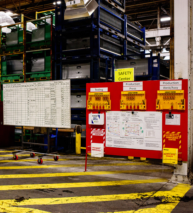 Whiteboard on the left with multiple columns and rows with checks and various notes. On the right, a large red board with the title Safety Center.